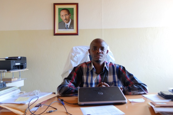 Sheikh Musa Sindayigaya is sitting behing his laptop in an office of the Muslim health centre in Kigali. On the wall is a picture of the Rwandan president Paul Kagame. Many different documents are lying on the desk. a docotr's white coat is slung over the chair.