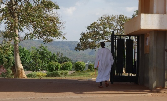 A man wearing a white Muslim dress enters a mosque's yard. The background of the picture shows the hilly Rwandan landscape.