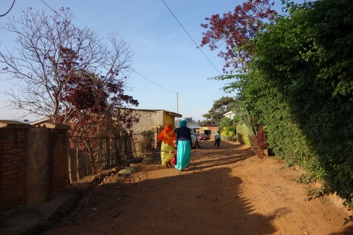 Two women with headscarves are walking through an unpaved road in the Muslim quarter Nyamirambo.