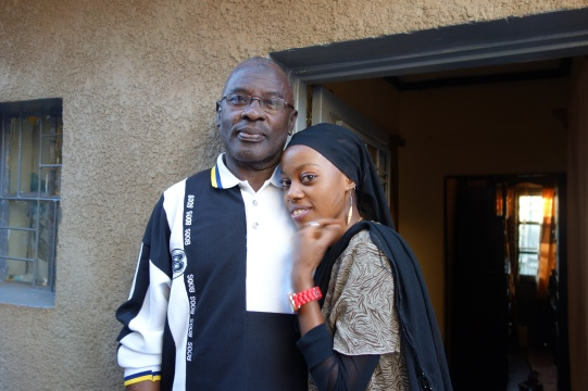 Yahaya Nesengiyumva is standing in front of the door of his house. Next to him one of his daughters.