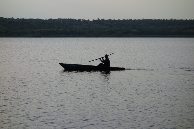 A fisherman in his boat on lake Kivu during sunset