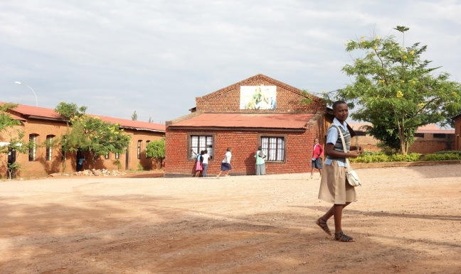 A Rwandan girl wearing a school uniform on an unpaved road. In the background: The buildings of a Christian school