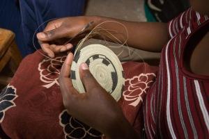 A Rwandan woman sitting on a chair is weaving a traditional Rwandan basket.